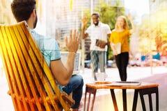 Les jeunes ondulant en voyant leur ami se reposer dans seul un café Photographie stock