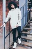 Les jeunes ont à la mode habillé l'homme dans un équipement frais posant sur un escalier en métal Photos libres de droits