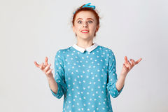 Les jeunes ont étonné et ont étonné la fille caucasienne faisant des gestes dans la pleine incrédulité, gesticulant ses épaules,  photographie stock libre de droits