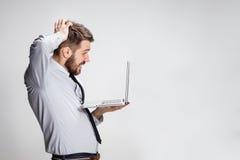 Les jeunes ont étonné l'homme avec son ordinateur portable Image stock