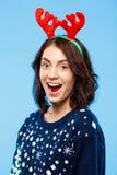 Les jeunes ont étonné la belle fille de brune dans des andouillers knited de renne de chandail et de Noël souriant au-dessus du f Photographie stock