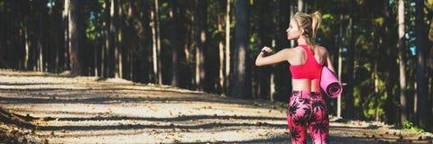 Les jeunes ont adapté la femme sportive dans une forêt utilisant la montre intelligente et tenant le tapis de yoga, marchant à pa photos libres de droits
