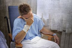 Les jeunes ont blessé l'homme pleurant dans la chambre d'hôpital reposant seul pleurer en douleur inquiétés pour son état de sant photos stock