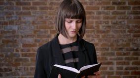 Les jeunes ont concentré la femme avec le livre de lecture court de coupe de cheveux et la position près du mur de briques banque de vidéos