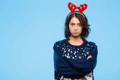 Les jeunes ont dérangé la belle fille de brune dans des andouillers knited de renne de chandail et de Noël au-dessus de fond bleu Photos stock