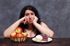 Les jeunes ont dérangé la femme de poids excessif ennuyée des régimes choisissant entre le hea photographie stock libre de droits