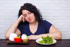 Les jeunes ont dérangé la femme de poids excessif ennuyée des régimes choisissant entre le hea photo libre de droits