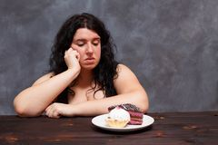 Les jeunes ont dérangé la femme de poids excessif ennuyée des régimes regardant sur des bonbons, c photos stock