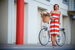 Les jeunes ont d'une manière élégante habillé la femme avec la bicyclette et l'a photos stock
