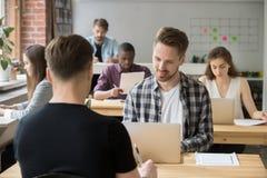Les jeunes ont en passant habillé des employés au travail dans coworking partagé  Images libres de droits