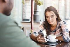 Les jeunes ont ennuyé le café potable de fille la date à un café Photo libre de droits