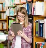 Les jeunes ont focalisé l'étudiant à l'aide d'une tablette dans une bibliothèque Photo libre de droits