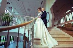 Les jeunes ont juste marié des couples dans des costumes de mariage étreignant sur une échelle Images libres de droits