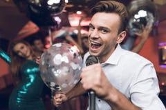 Les jeunes ont l'amusement dans une boîte de nuit et chantent dans le karaoke Dans le premier plan est un homme dans une chemise  Photos libres de droits