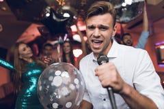 Les jeunes ont l'amusement dans une boîte de nuit et chantent dans le karaoke Dans le premier plan est un homme dans une chemise  Photographie stock libre de droits