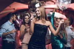Les jeunes ont l'amusement dans une boîte de nuit et chantent dans le karaoke Dans le premier plan il y a une femme dans une robe Photo libre de droits