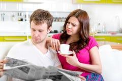 Les jeunes ont marié des couples dans des pyjamas se reposant dans le sofa avec le newspap Photo libre de droits