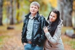 Les jeunes ont marié les couples enceintes marchant en parc d'automne photo stock