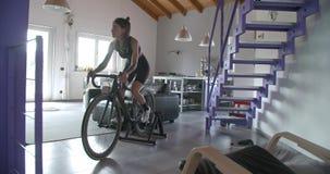 Les jeunes ont tatoué la femme de cycliste faisant un cycle avec la séance d'entraînement de sport de forme physique de bicyclett banque de vidéos