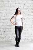 Les jeunes ont tatoué la femme utilisant le T-shirt vide, se tenant devant le mur de briques dans le grenier photos libres de droits