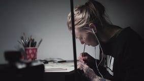 Les jeunes ont tatoué le dessin punk de femme d'artiste au bureau dans la lumière de lampe clips vidéos