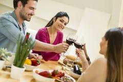 Les jeunes ont un repas dans la salle à manger dans la maison moderne Photos stock