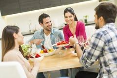 Les jeunes ont un repas dans la salle à manger dans la maison moderne Image libre de droits