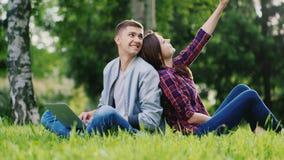 Les jeunes ont un repos sur la nature Un homme utilise un ordinateur portable, fille faisant le smartphone de selfie clips vidéos