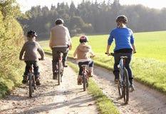 Les jeunes parents avec des enfants conduisent des vélos en stationnement Photos libres de droits