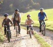 Les jeunes parents avec des enfants conduisent des vélos en stationnement Image libre de droits