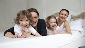 Les jeunes parents de sourire avec deux enfants ont l'amusement ensemble dans leur chambre à coucher Famille joyeuse sur le lit b banque de vidéos