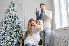Les jeunes parents dupent autour et jouent avec peu de fils Famille heureux ayant l'amusement à la maison Matin de Noël dans la v images libres de droits