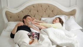 Les jeunes parents endormis se trouvent sur le lit La petite fille mignonne jette un oreiller dans le père et la mère Famille heu banque de vidéos