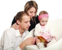 Les jeunes parents et bébé ont lu le magazine photographie stock libre de droits