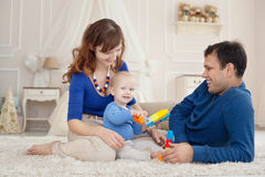 Les jeunes parents et le fils mignon jouent le kit de bâtiment se reposant sur un tapis chez la pièce des enfants Photographie stock libre de droits