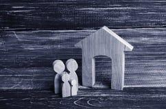 Les jeunes parents et un enfant se tiennent près de leur maison Concept image libre de droits