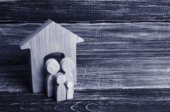 Les jeunes parents et un enfant se tiennent près de leur maison Concept images stock