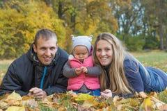 Les jeunes parents heureux avec son enfant se trouvent au sol se surpassent Photos stock