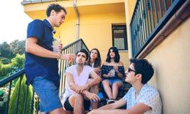 Les jeunes parlant se reposer dehors sur les escaliers à la maison font un pas Photo libre de droits