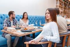 Les jeunes passent le temps dans un café mangeant et buvant Images libres de droits