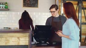 Les jeunes payant le café à emporter avec le smartphone et parlant au cashie amical tandis que barman femelle attrayant clips vidéos