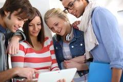 Les jeunes pendant la coupure dans la classe utilisant le comprimé Images libres de droits
