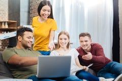 Les jeunes positifs souriant tout en regardant l'écran de leur ordinateur portable Image stock