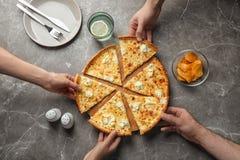 Les jeunes prenant des tranches de pizza de fromage savoureuse à la table Photo libre de droits