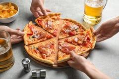 Les jeunes prenant des tranches de pizza savoureuse Image stock