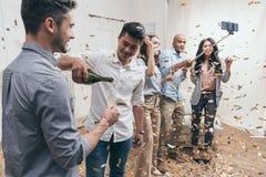 Les jeunes prenant le selfie tout en célébrant avec le champagne et les confettis Images stock