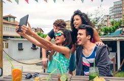 Les jeunes prenant un selfie avec le comprimé en partie Images libres de droits