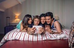 Les jeunes prenant un selfie se trouvant au-dessus du lit Photographie stock