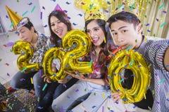 Les jeunes prennent la photo avec les numéros 2020 photographie stock