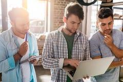 Les jeunes professionnels travaillant aux affaires nouvelles projettent avec l'ordinateur portable dans le bureau de petite entre Photographie stock